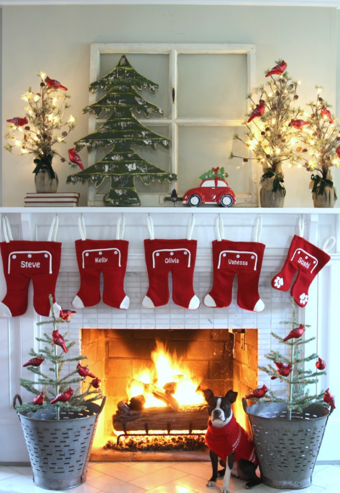 five red and white rompers, hanging on a white mantelpiece, decorated with several small christmas tree ornaments, and a small red car, fireplace decor