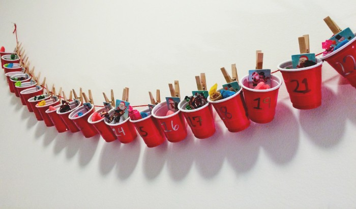plastic cups in red and white, filled with candy and small gifts, attached with wooden clothes pegs, to a red piece of string, hanging on a white wall