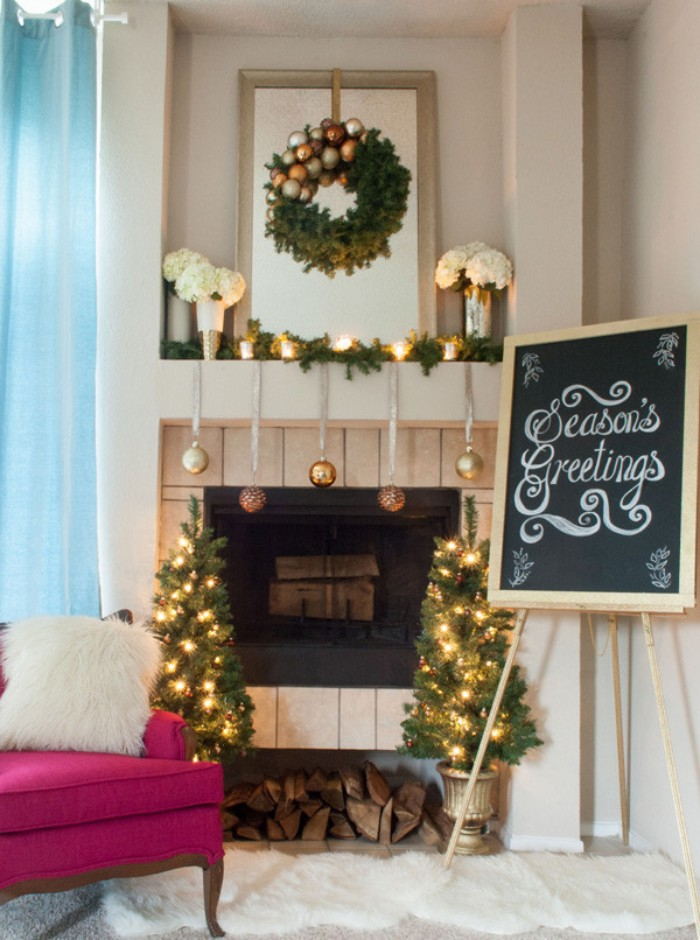 easel supporting a framed blackboard, with the inscription, season's greetings, written in white chalk, next to a fireplace, adorned with gold and silver baubles, and burning candles, fireplace mantel decor