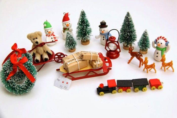 various small toys and decorations, to put in an advent calendar, miniature christmas wreaths and trees, teddy bear on a sleigh, small deer and snowmen figurines, a sleigh with presents, and others