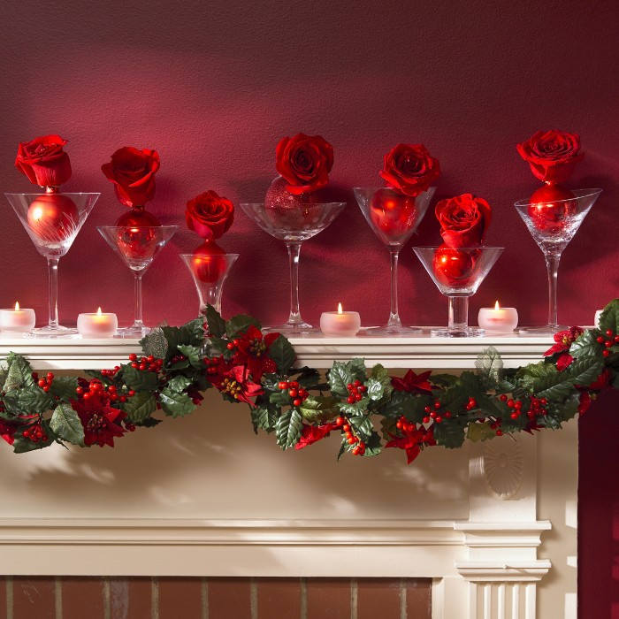 cocktail glasses with different designs, placed on a white mantel, near burning tea lights, christmas mantel ideas, each glass contains a red rose, attached to a red christmas bauble