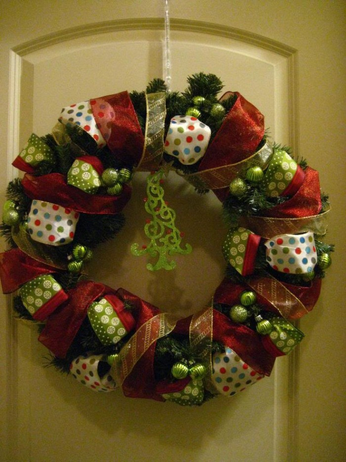 several kinds of ribbon, white with multicolored polka dots, sheer red and thin sheer yellow, wrapped around a green wreath, made from faux pine branches