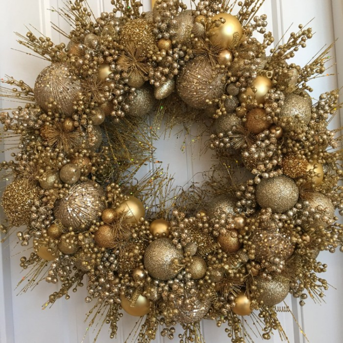 gold wreath made from round, christmas ornaments in different sizes, and thin faux branches, with multiple tiny berries, all in gold hues