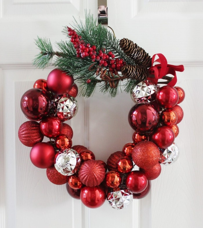 red and silver christmas tree baubles, stuck together to form awreath, decorated with pine branches, red berries and pine cones, christmas wreath images, on a white door