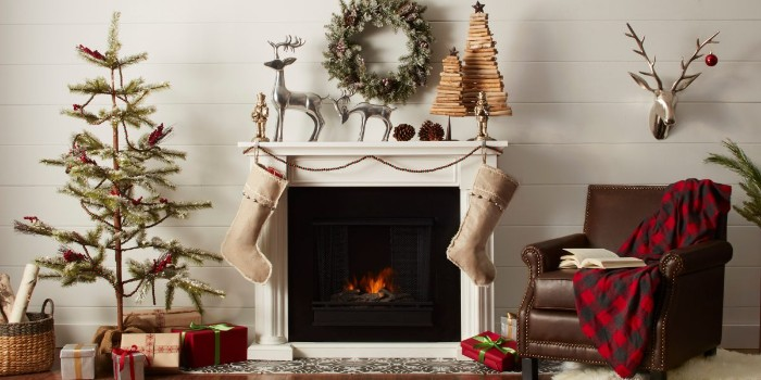 thin christmas tree, with very simple decorations, inside a nordic style room, with a white and black fireplace, christmas mantel ideas, beige stockings and festive decorations