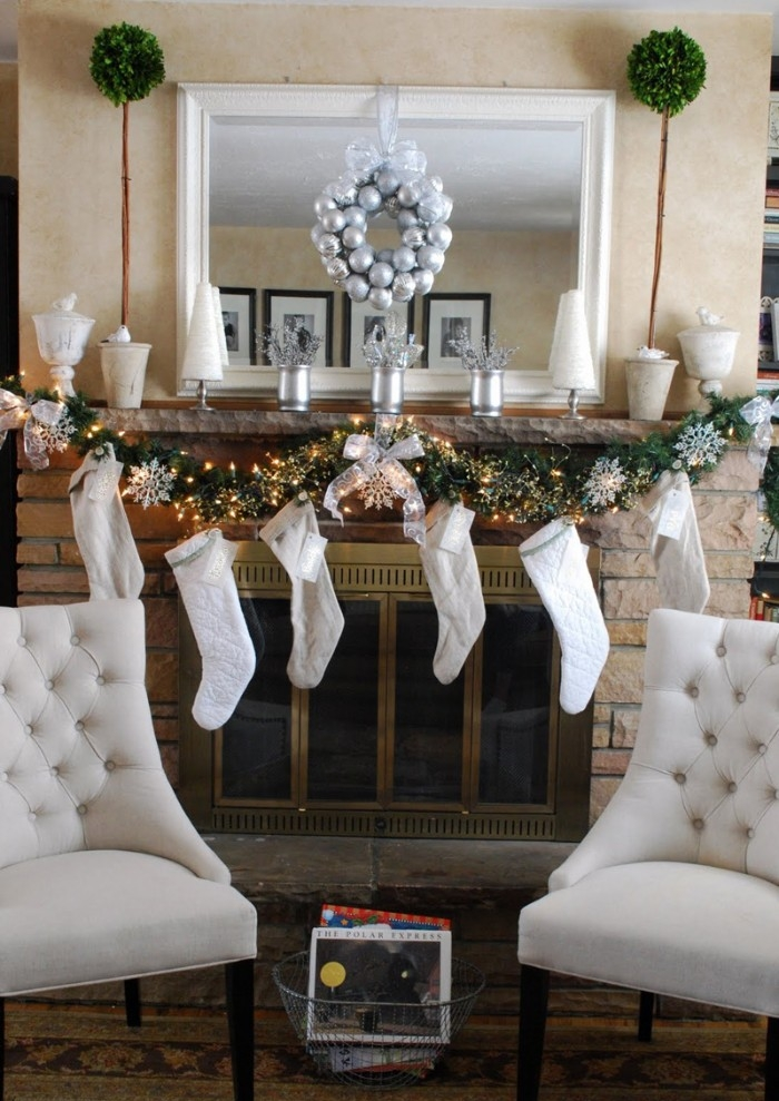 six white stockings, hanging from a mantel, with a garland, featuring lit string lights, and silver snowflake ornaments, fireplace mantel decor, small wreath made from silver baubles