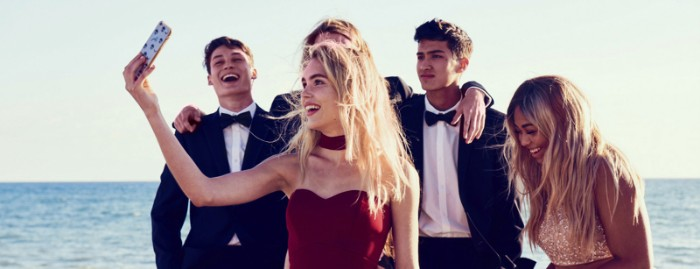 group of laughing teenagers, standing by the sea, blonde young woman, dressed in a dark red gown, holding her phone up for a selfie