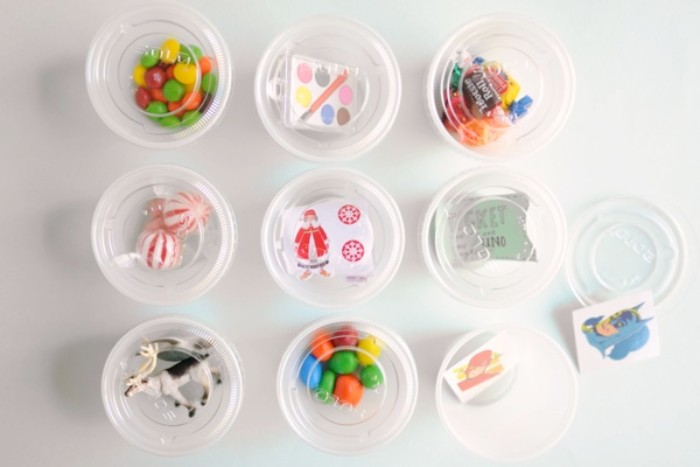 nine small round, plastic boxes with transparent lids, or candy containers, filled with different sweets, and small toys, advent calendar made at home