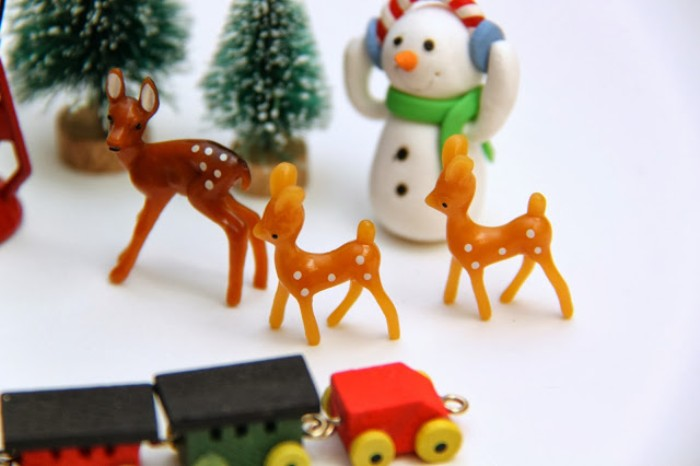 deer figurines made of brown plastic, near a snowman toy, several tiny christmas trees, and a miniature wooden train, advent calendar stuffings