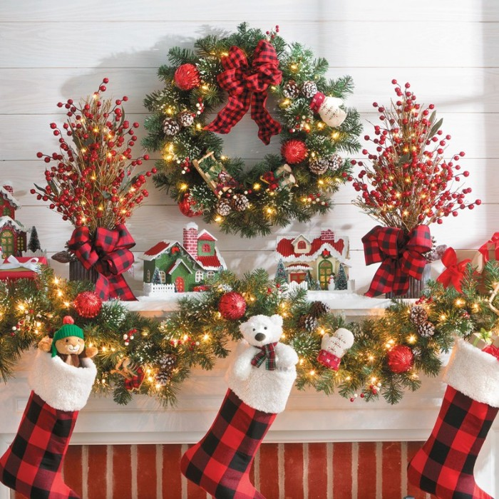 images of christmas, three stockings stuffed with toys, hanging on a lavishly decorated mantel, with garlands and a wreath, small house figurines and more