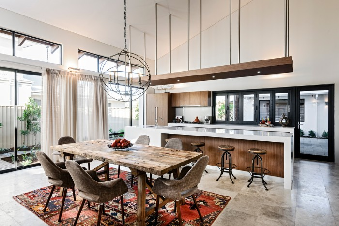 open plan dining area and kitchen, featuring a rustic wooden table, several mink brown chairs, a kilim rug, and large double windows, kitchen island with bar chairs