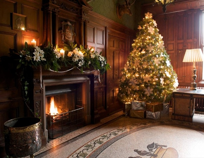 mantel decor with green leaves, and white flowers, in an antique style room, with brown wood paneling, and a classic christmas tree