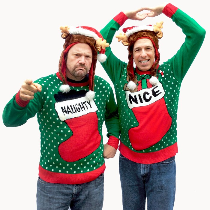 green jumpers with white polka dots, and red and white christmas stockings, one saying naughty and the other nice, ugly christmas sweater ideas, on two men, wearing hats with small fabric deer antlers