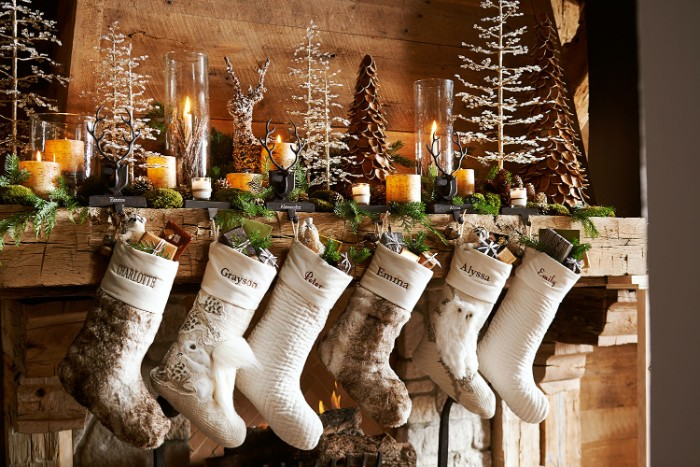 delicate ornaments shaped like thin, white christmas trees, burning candles and a leafy green garland, on a rustic wooden fireplace, mantel decor, six white and beige stockings
