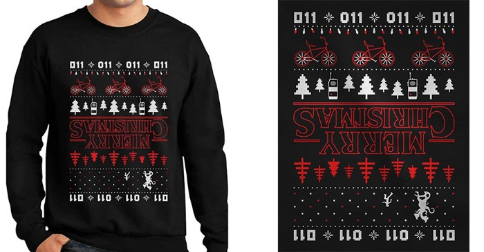 sweater inspired by the tv show stranger things, black with a christmas-like pattern, featuring bikes and xmas trees, walkie talkies and numbers, and the words mery christmas, turned upside down