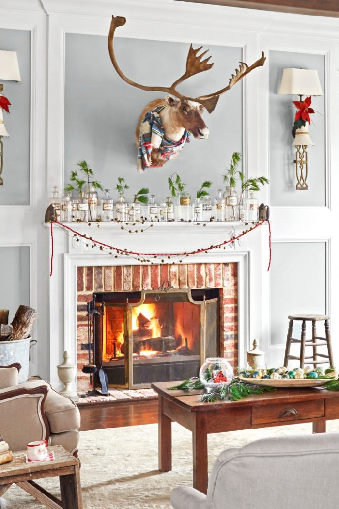 moose's head stuffed, and decorated with a winter scarf, mounted on a grey and white wall, above a fireplace, decorated with multiple jars, containing pine branches, holiday images, burning fire and festive ornaments