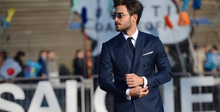 smart navy suit, worn over a white shirt, and a black tie, by a young man with sunglasses, a moustache and stubble on his chin, cocktail attire ideas for guys