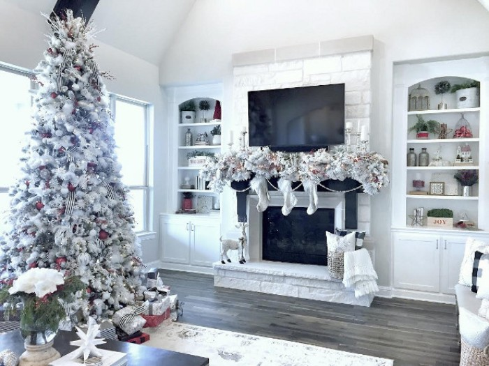white and silver christmas decorations, draped over a black and white fireplace, christmas mantel ideas, a tall faux christmas tree in white standing nearby