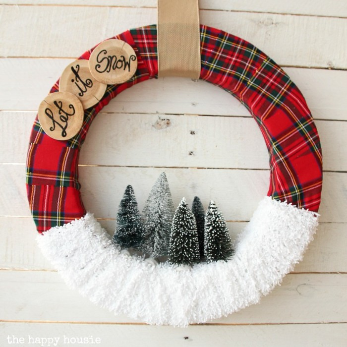 let it snow, written in black, on three round wooden tags, stuck onto a wreath, covered in red tartan fabric, and white gauze, christmas wreath images, five snowy christmas tree figurines in the middle