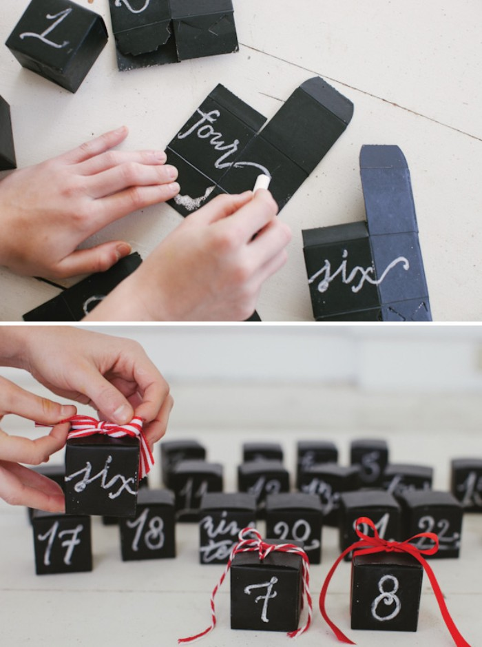 the word four, being written in white chalk, on a black piece of card, more pieces of black card nearby, diy advent calendar, next image shows several black boxes, with white numbers, and red ribbon bows