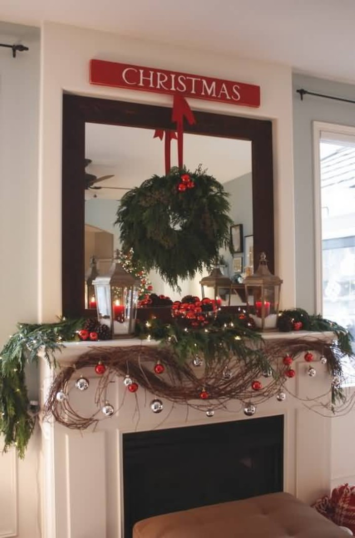 baubles in silver and red, hanging from a garland, made from brown, and green artificial branches, draped over a white fireplace mantel, green pine wreath, with red details, hanging on the large mirror overhead