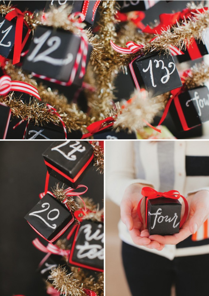 close up of a gold, faux christmas tree, decorated with small, black cube-shaped boxes, decorated with numbers written in white chalk, and red ribbon tied in bows, diy advent calendar, hand holding one of the boxes
