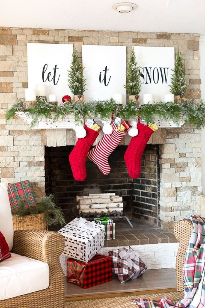 fireplace mantel decor, featuring three white canvases, with the words, let it snow, written in black cursive, a green garland, and three red and white stockings