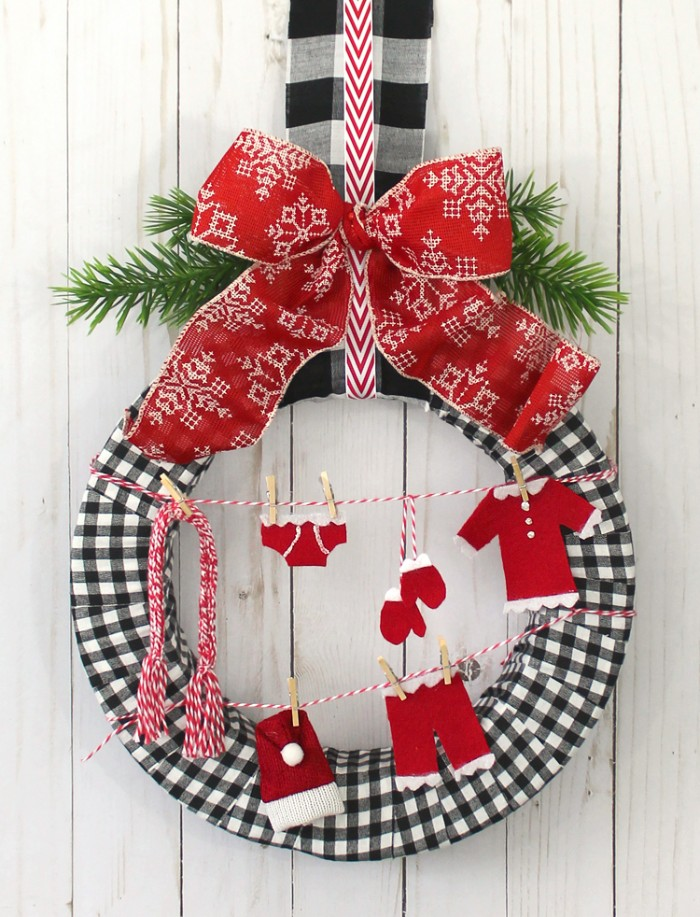 washing lines made from striped, red and white yarn, featuring small red and white clothes, hanging on miniature pegs, christmas wreath ideas, on a wreath covered in black and white checkered fabric, and decorated with a large red and white bow, and pine leaves