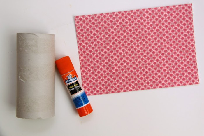 what you will need, to make a small gift box, for a diy advent calendar, a pale beige, cardboard paper toilet roll, a sheet of patterned origami paper, in red and white, and a glue stick