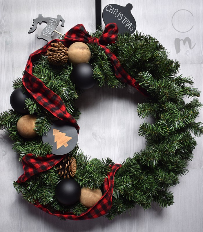 fake fir diy christmas wreath, decorated with black and beige christmas tree baubles, pinecones and a red and black, checkered ribbon tied into a bow, small black shapes, with the words merry and christmas, written in white chalk