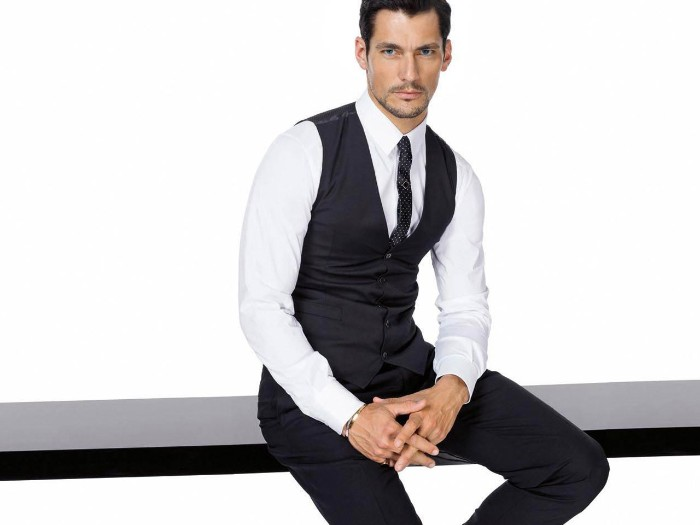 cocktail attire for men, brunette man with short beard and mustache, sitting on a black surface, dressed in black trousers, a smart black vest, white shirt and a dark patterned tie