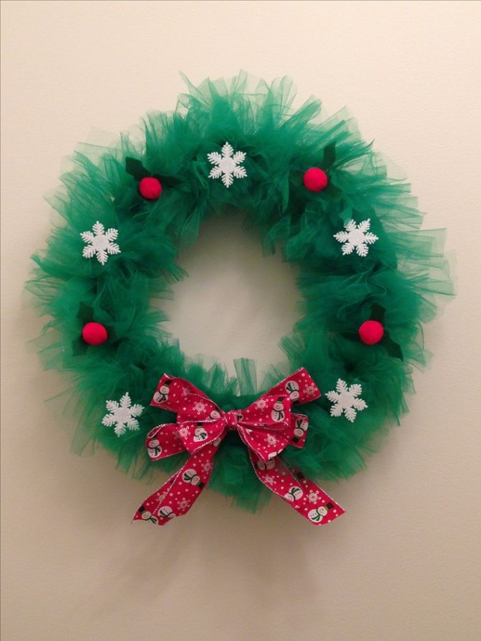 forest green tulle, shaped into a christmas wreath, decorated with white snowflake ornaments, wreath ideas, red pattrened bow, and red holly berries, with green leaves, made from felt