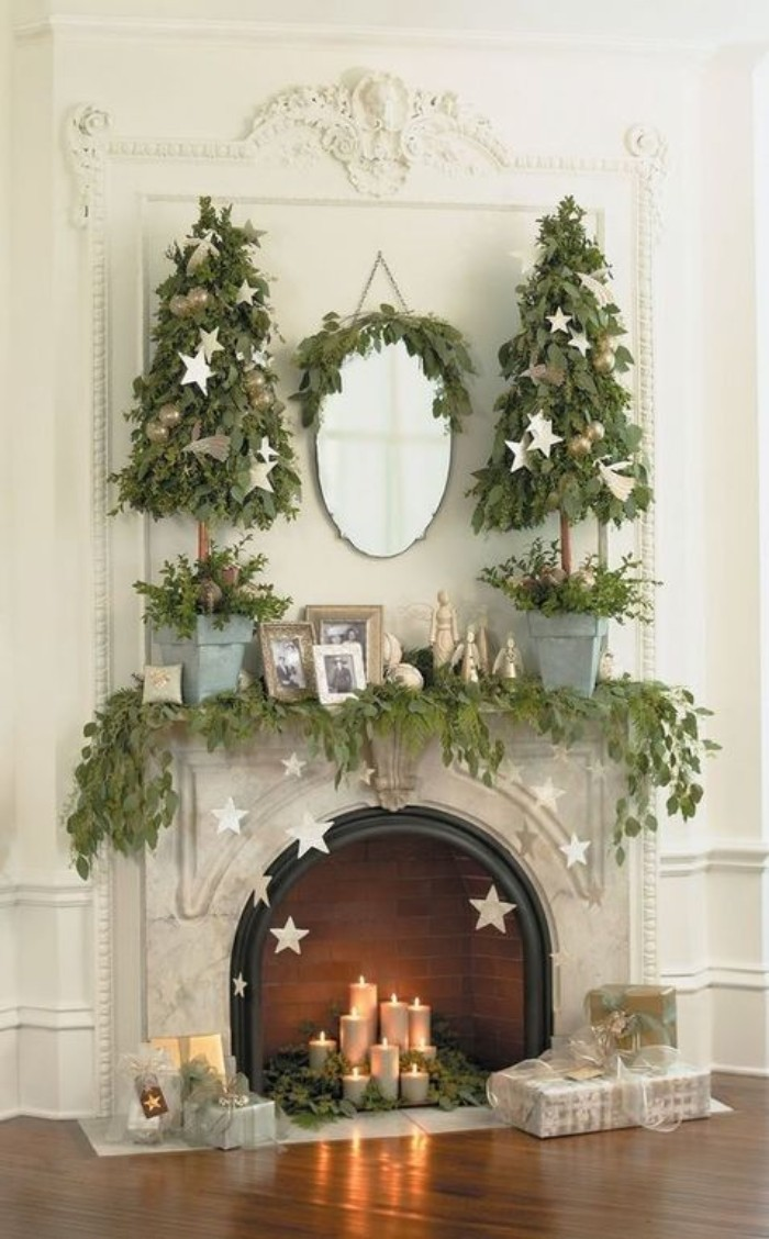 star-shaped ornaments in silver, suspended from the mantelpiece, of a classic fireplace, covered in green garlands, made of leaves, fireplace mantel decor, burning candles and two small christmas trees