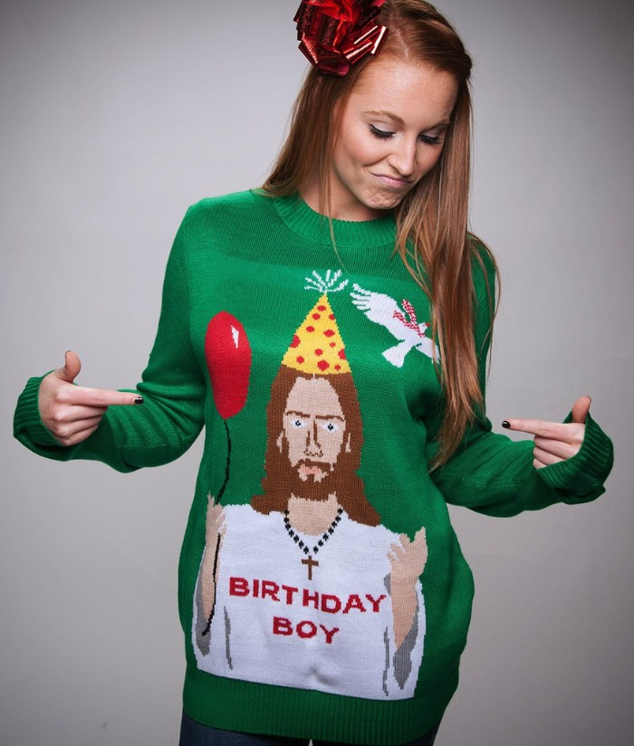 jesus holding a balloon, and wearing a party hat, a cross necklace, and a white t-shirt with the words birthday boy, written in red, on a green jumper, also featuring a white dove, girls ugly christmas sweater, on a slim brunette young woman