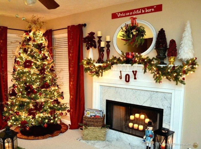 tall christmas tree, covered in red ornaments, gold garlands and glowing dairy lights, in a living room, with a white marble-effect fireplace, containing lit candles, diy fireplace mantel, with a pine garland