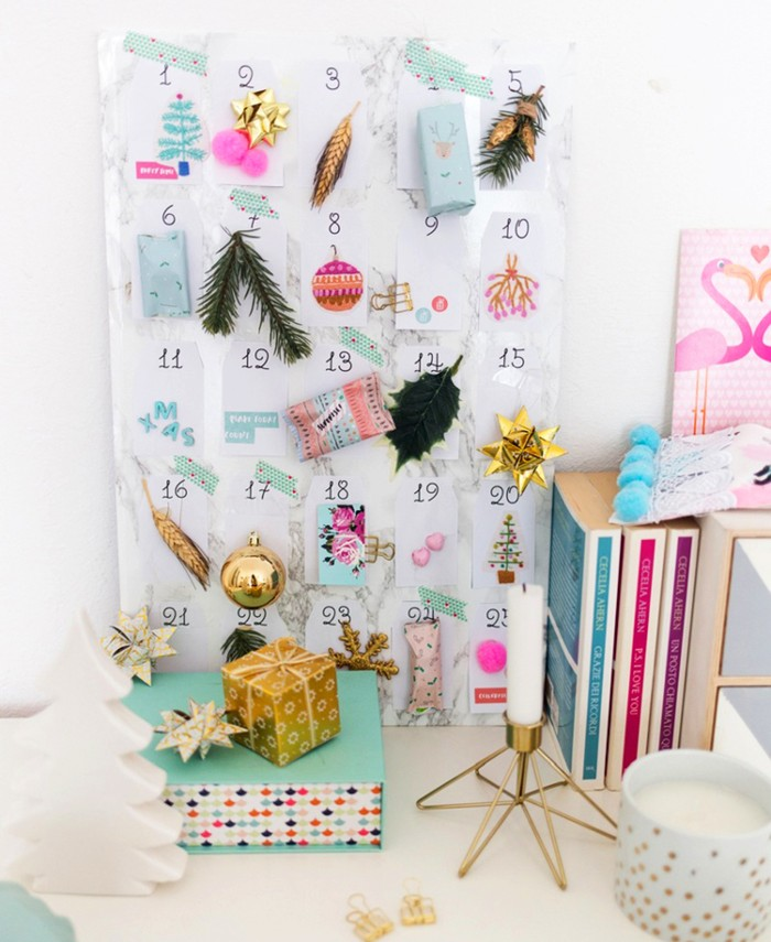 assortment of christmas ornaments, cards and little fir tree branches, stuck to 25 white pieces of paper, christmas countdown calendar, attached to a white board, with a pale grey marble pattern