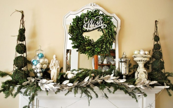 wish written in silver, on an ornament, decorating a simple green wreath, hung over a mirror, above a white mantelpiece, holiday images, pine sprigs and a decorative branch with silver leaves