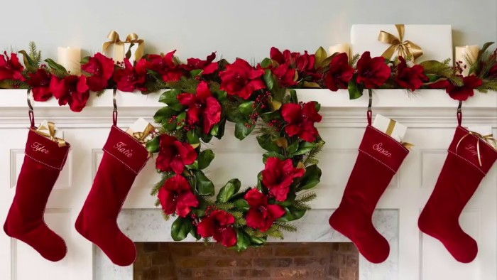 burgundy velvet stockings, each inscribed with a name, hanging on a white mantelpiece, near a green wreath with faux red flowers, christmas mantel ideas, similar red and green garland in the background