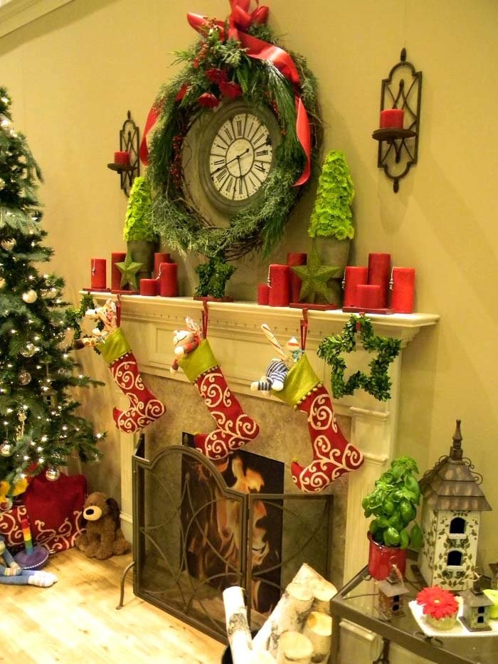 round old-looking clock, surrounded by a green pine garland, and red candles, images of christmas, above a fireplace, with three red, white and lime green stockings