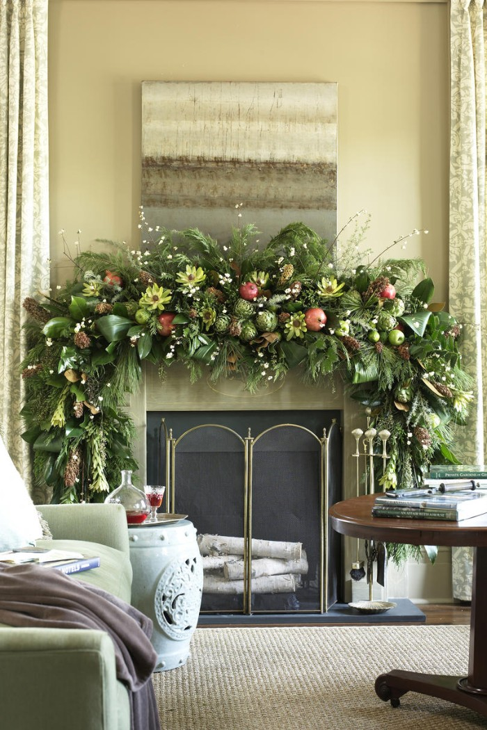 yellow flowers and red pomegranates, green apples and various leaves, on a lush green garland, decorating a diy fireplace mantel, in a room with beige walls