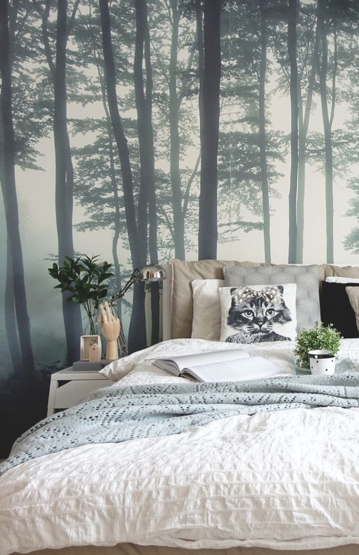 misty forest scene, in dark grey and white, on a wallpaper behind a bed, covered in white, grey and beige cushions, duvet and blanket