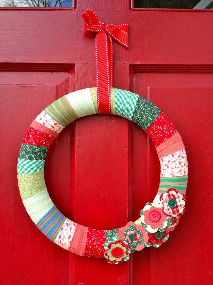 simple wreath made from a hoop, covered with patterned, and plain washi tape, in different colors, and decorated with colorful paper flowers and buttons, christmas wreath ideas, on a red door