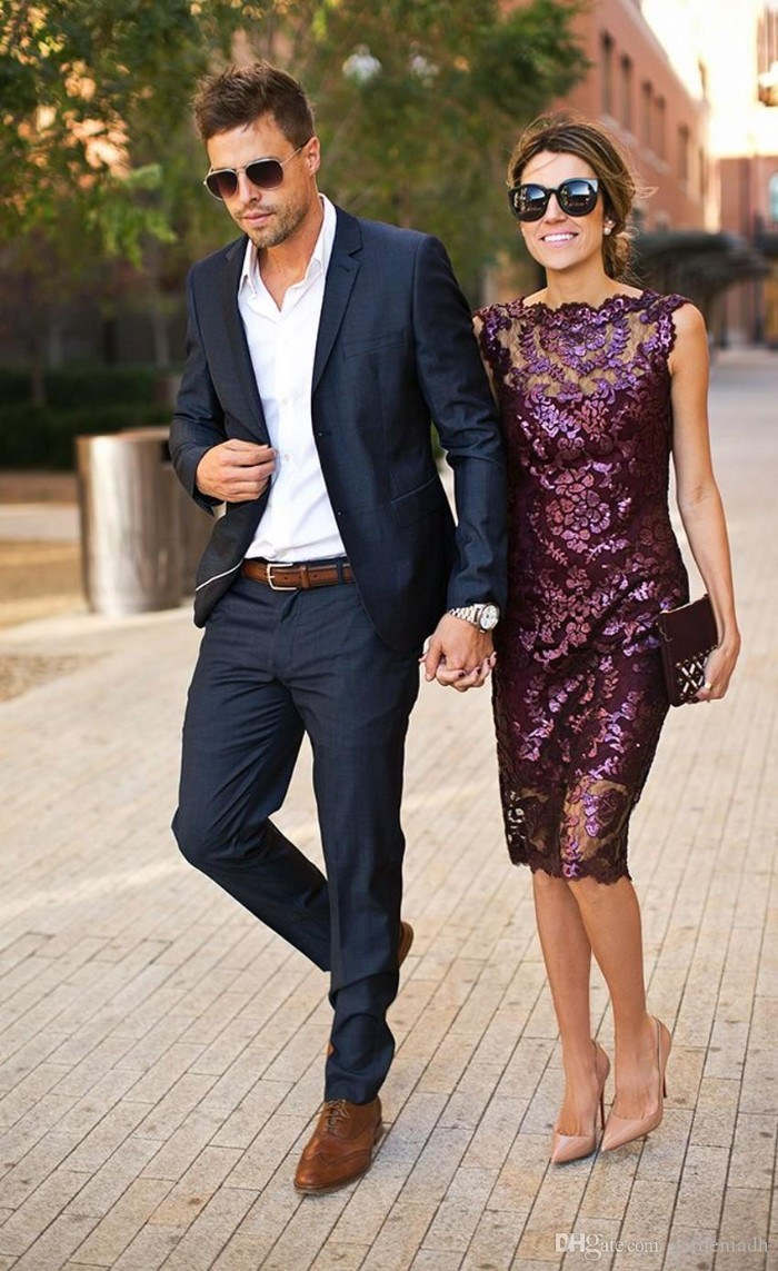 shiny purple midi dress, with lace details and sequins, worn by a smiling brunette woman, with sunglasses and nude beige shoes, walking hand in hand with a man, dressed in a navy suit, and a white shirt, cocktail attire for women