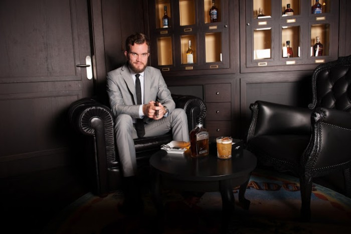smiling man in a light grey suit, with a white shirt, and a dark tie, sitting on a black leather armchair, near a small wooden table, with drinks and a snack, cocktail attire examples for men