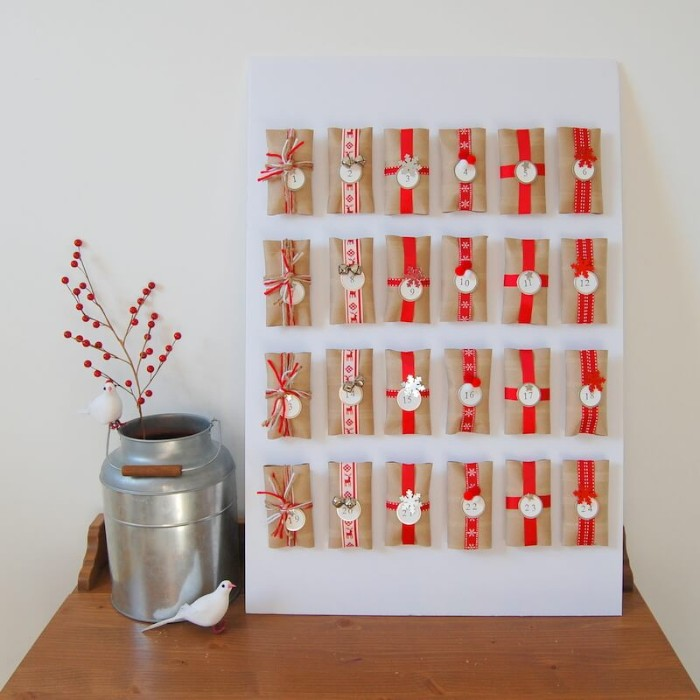 twenty four small gifts, wrapped in beige paper, and decorated with red patterned, and plain ribbons, and round numbered labels, attached to a rectangular white board, advent calendar ideas