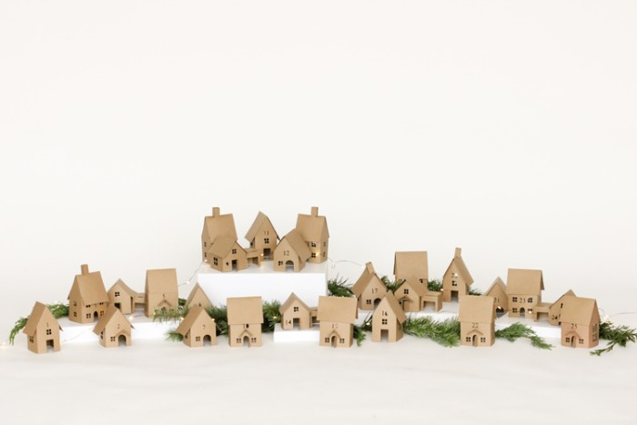 multiple small houses, made from beige card, placed on a white surface, decorated with lit string lights, and pine branches, adult advent calendar diy, decorative christmas village