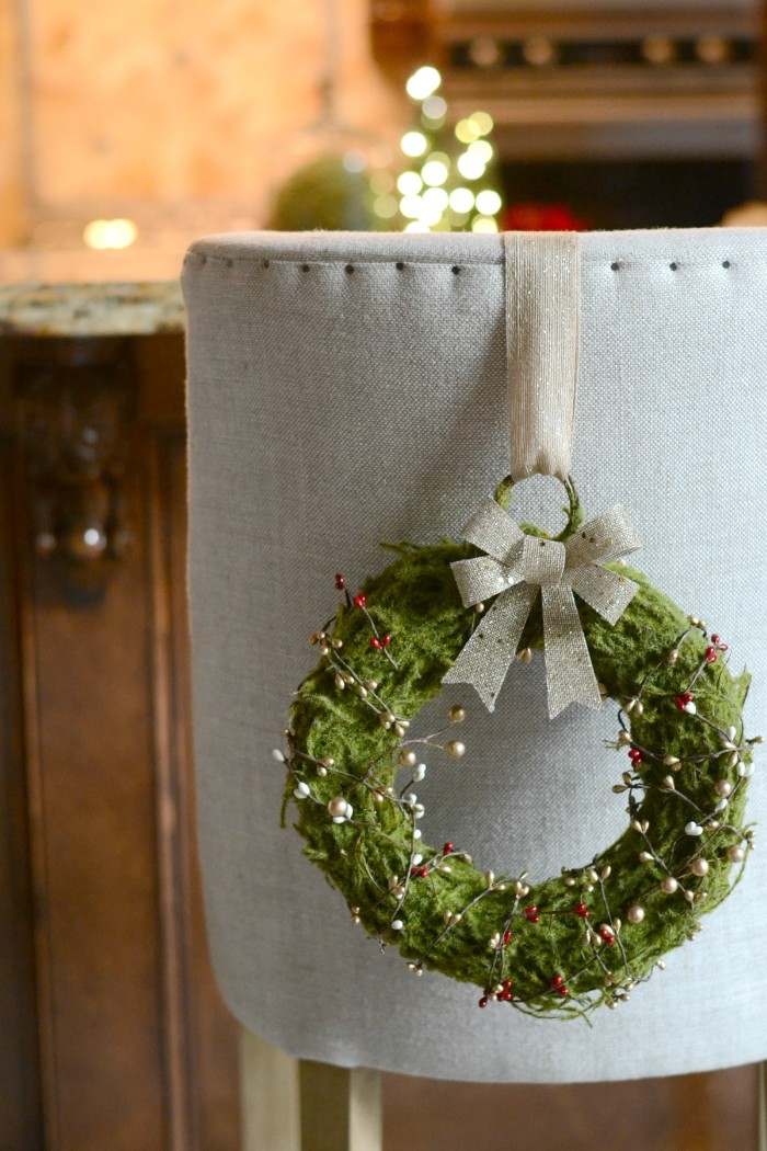 christmas wreath images, green wreath covered by a mossy texture, and decorated with twisted wire, featuring red and white faux berries, hanging on a grey armchair