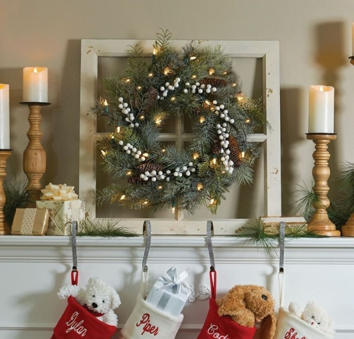 wooden candlesticks holding three lit candles, near a christmas wreath, decorated with small glowing fairy lights, and white faux berries, christmas mantel ideas