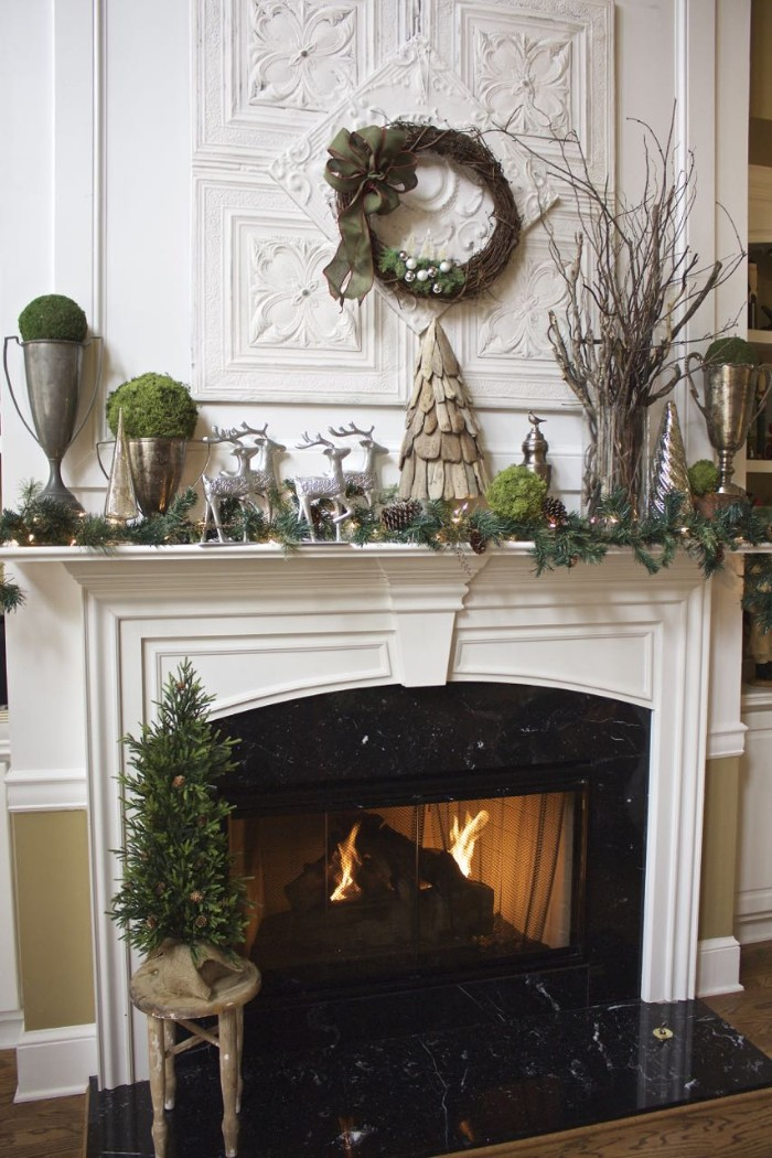 minimalistic diy fireplace mantel decoration, featuring a handmade, wooden christmas tree figurine, a vase with dried branches, four silver reindeer statuettes, pine leaves and pine cones