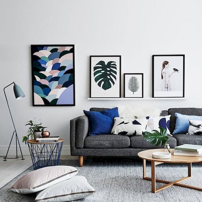 white wall, minimalist paintings, wooden floor with grey carpet, dark grey couch with printed blue and white throw pillows, small wooden coffee table, small living room decorating ideas